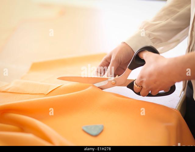 Fashion designer cutting cloth in fashion design studio, close up - Stock Image