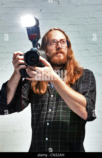 Photographer with flash on camera - Stock Image