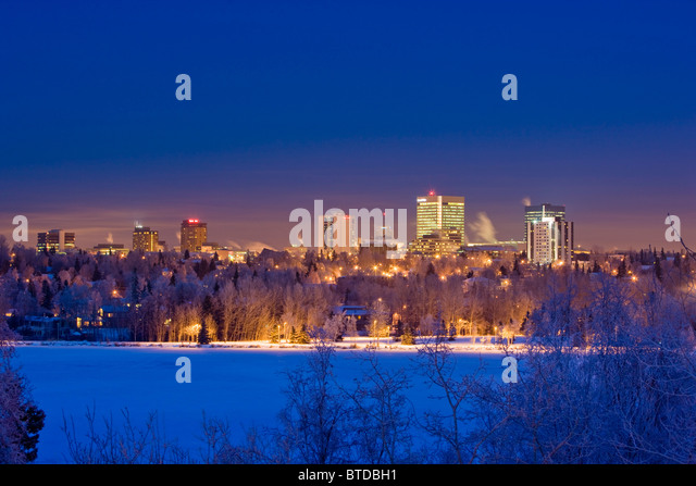 Skyline view of downtown Anchorage and Westchester Lagoon at twilight, Southcentral Alaska, Winter - Stock Image
