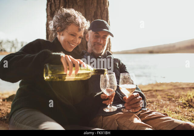 Senior couple enjoying drinks at campsite near Lake. Mature woman pouring wine in glasses, both sitting under a - Stock-Bilder