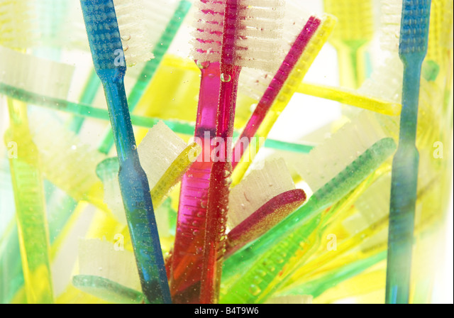 close up of submerged and floating brightly coloured toothbrushes in glass vase - Stock Image