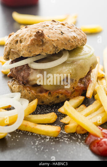 Homemade cheeseburger with french fries, onion slices - Stock Image