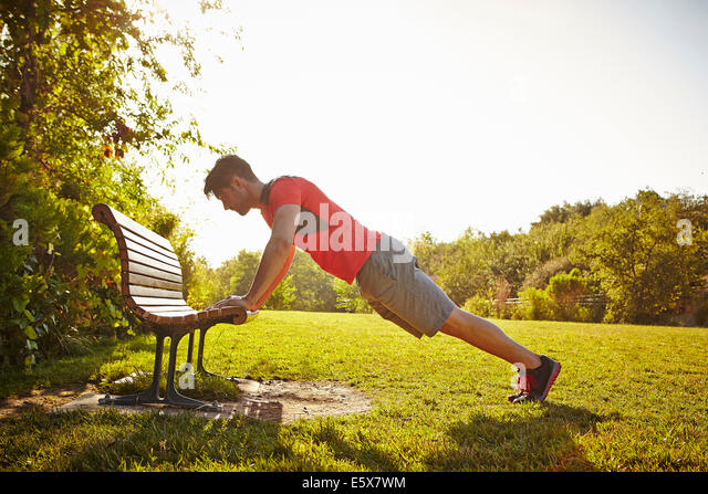 Young male runner doing push ups on park bench - Stock Image