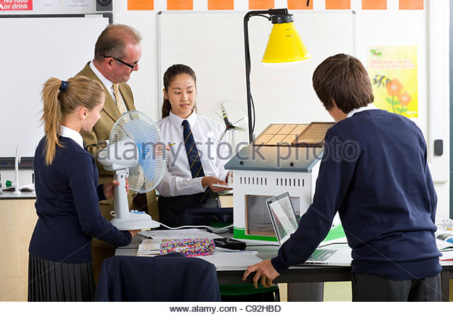 Teacher and students in school uniforms with wind turbine and solar panel models in science class - Stock Image