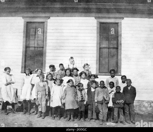 Full length landscape shot of schoolchildren outdoors, six African American students in the cluster on the right, - Stock Image