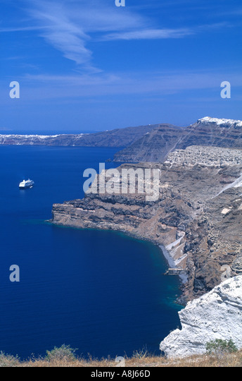 GREECE Santorini caldera dramatic view of the steep cliff sides with the Mediterranean and tiny cruise ship in distance - Stock Image
