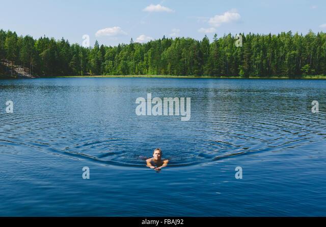 Finland, Uusimaa, Espoo, Lake Kvarntrask, Young man swimming in lake - Stock-Bilder