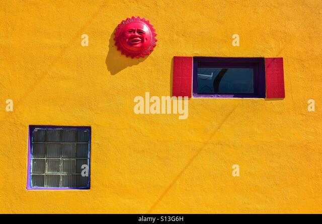 Red sun on yellow wall - Stock Image