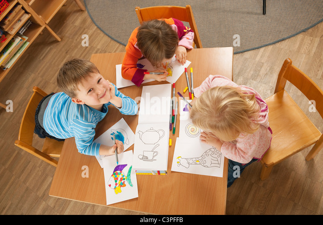 Germany, Children in nursery sitting at table drawing pictures, elevated view - Stock Image