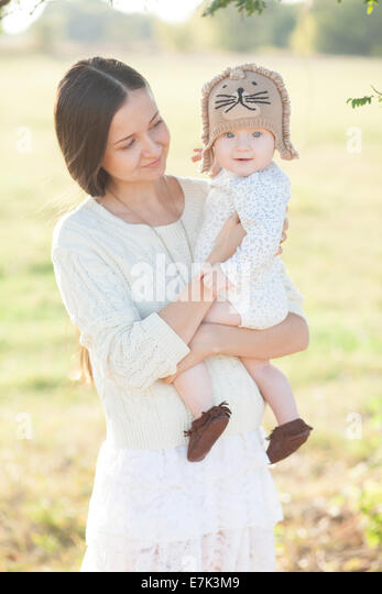 Pretty baby in arms - Stock Image