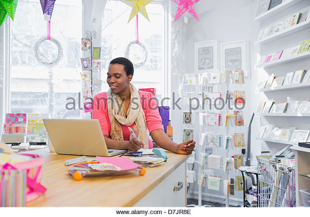 Female small business owner placing orders online - Stock Image