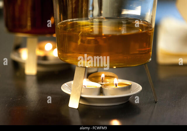 Burning candle warming the tea pot - Stock Image