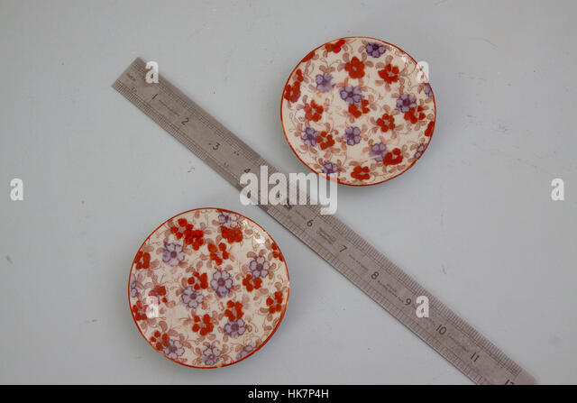 Small decorative saucers with ruler - Stock Image