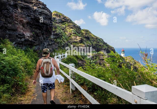 Rear view of young male tourist walking towards  Makapuu lighthouse, Oahu, Hawaii, USA - Stock-Bilder