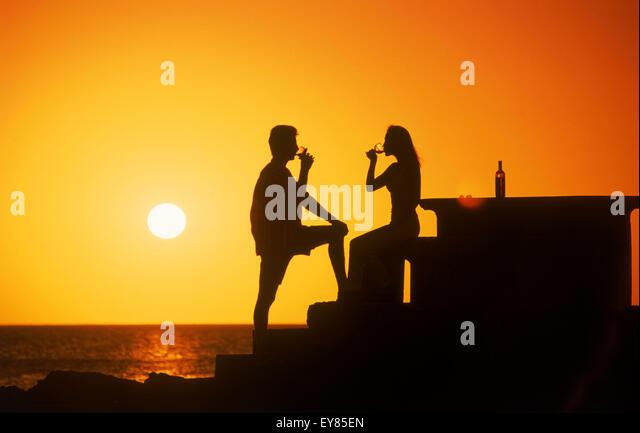 Couple enjoying a glass of wine at sunset along coast of Uruguay - Stock Image