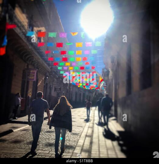 A couple of tourists walk in a street decorated with decorative paper flags in Guanajuato, Mexico - Stock Image