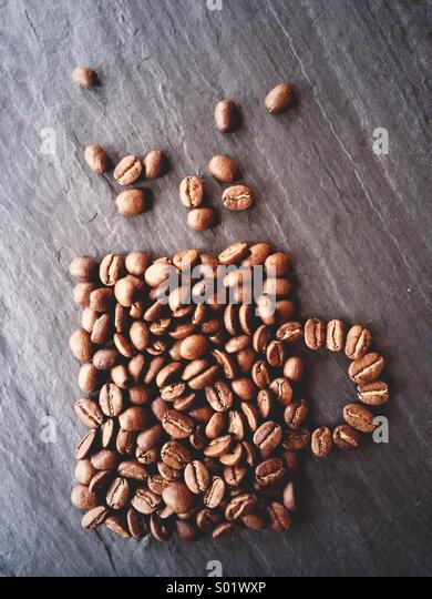 Coffee beans shaped to resemble a cup of coffee. - Stock Image
