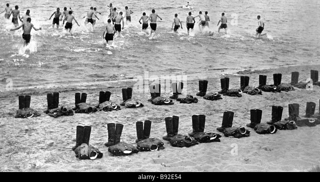 Soldiers bathing their uniforms left on the seashore - Stock Image