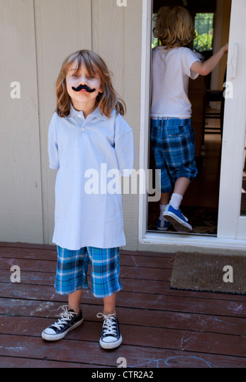 A little girl is standing on the deck wearing a fake mustache. - Stock Image