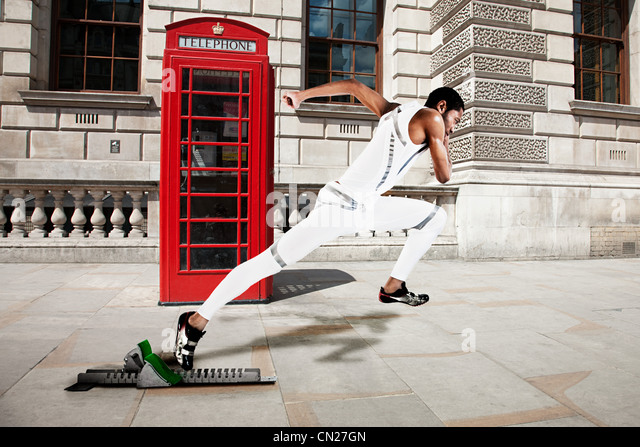 Olympic sprinter on starting line with red telephone box in background - Stock Image