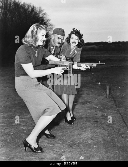 Two young women and a soldier trying out a machine gun - Stock Image