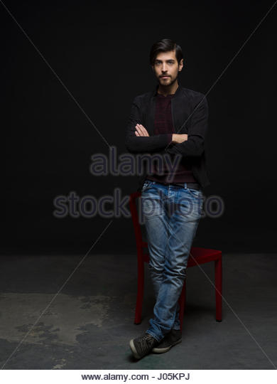 Portrait cool brunette man with beard and arms crossed against black background - Stock Image