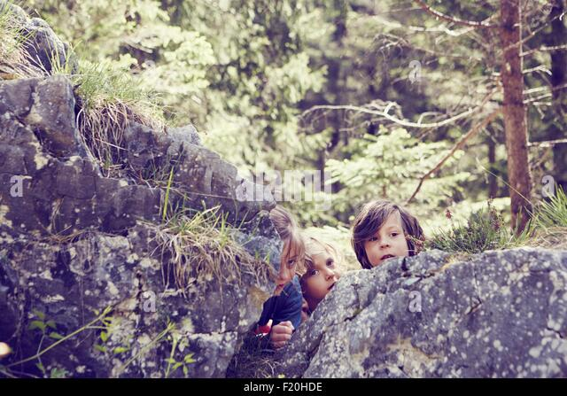 Three children hiding behind rocks in forest - Stock Image