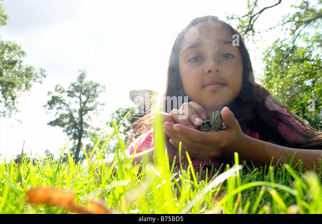 Low angle view, eight year old girl lying in grass with turtle, Winnipeg, Canada - Stock Image