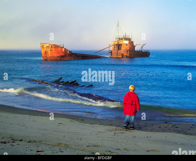 A boy views a shipwreck, Seal Island, Nova Scotia, Canada - Stock Image