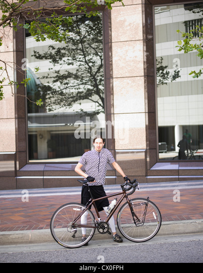 Man with Bicycle in front of Office Building - Stock Image