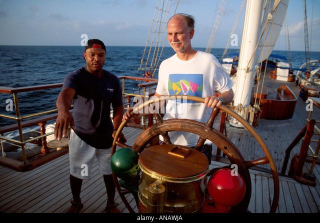 Venezuela Barefoot Windjammer SV Fantome passenger steering helm Black man crew schooner cruise - Stock Image