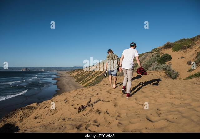 Two young men walking along sand, rear view - Stock Image