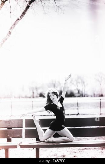 Dancer posing on park bench - Stock Image