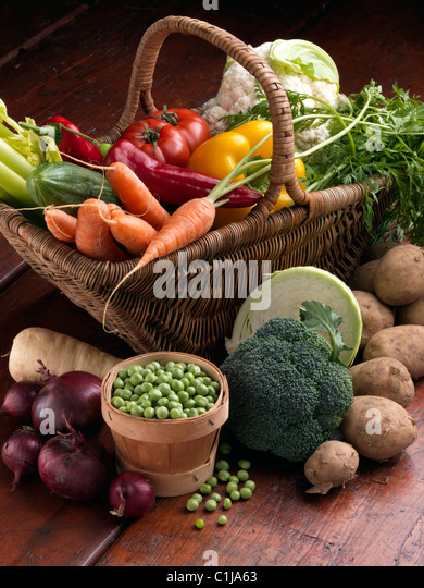 Wicker basket raw vegetables tomatoes sweet red yellow peppers carrots peas cauliflower parsnips broccoli cooking - Stock Image