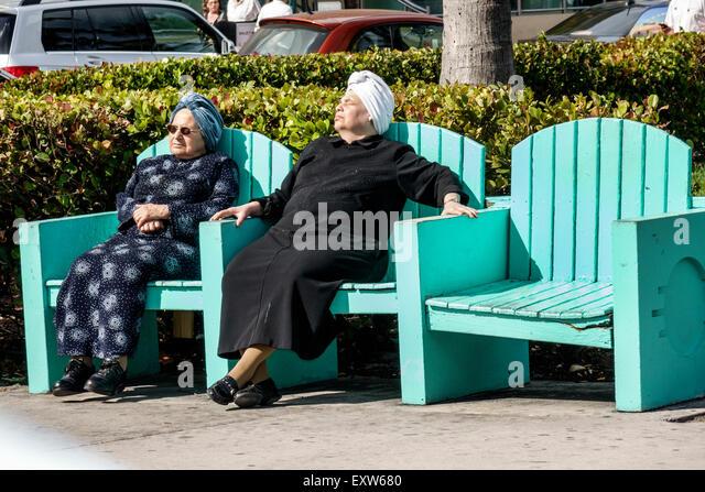 Miami Beach Florida senior woman friends sunning Lummus Park bench Orthodox Jews - Stock Image
