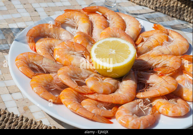 Plate of Prawns with Lemon juice on a round plate in the sunshine - Stock Image