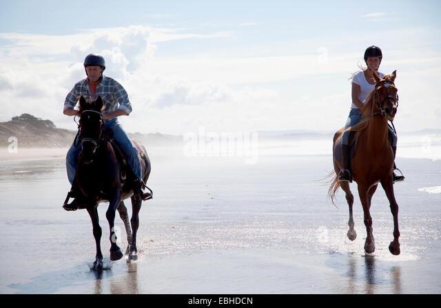 Horse riders galloping, Pakiri Beach, Auckland, New Zealand - Stock-Bilder