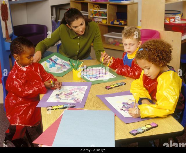 Preschool Teacher Showing Children How To Paint - Stock Image