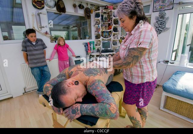 A woman tattooist works on a design on her husband's back, watched by their two bored children. - Stock-Bilder