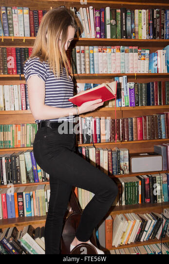 Young girl choosing books from home library shelves. - Stock Image