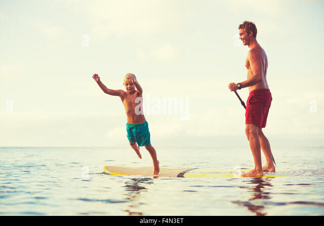 Father and son stand up paddling at sunrise, Summer fun outdoor lifestyle - Stock Image