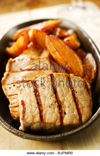 Grilled pork medallions with chips - Stock Image
