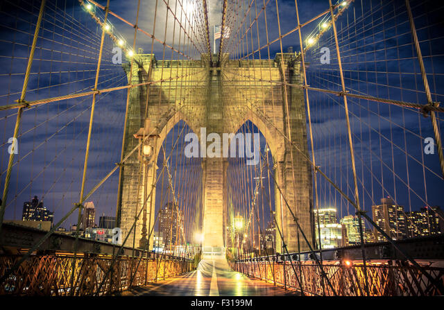 View of historic Brooklyn Bridge at night seen from the pedestrian walkway - Stock Image