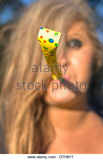 Woman Whistle Blower Celebrates The New Year By Blowing A Party Noisemaker - Stock Image