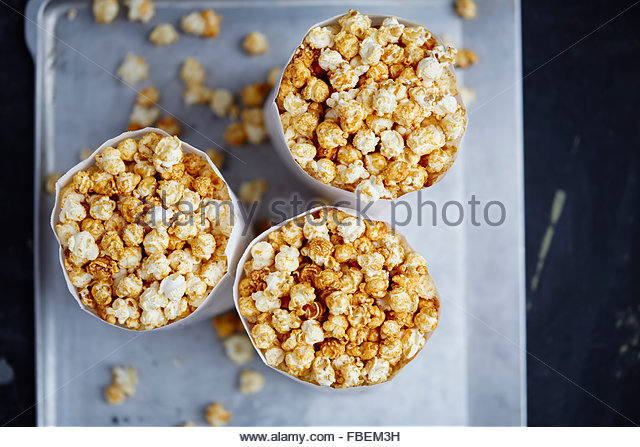 Tree paper bags full of popcorn on metal background - Stock Image