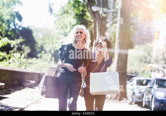 Young woman and her mentor shopping and laughing on street, New York City, USA - Stock Image