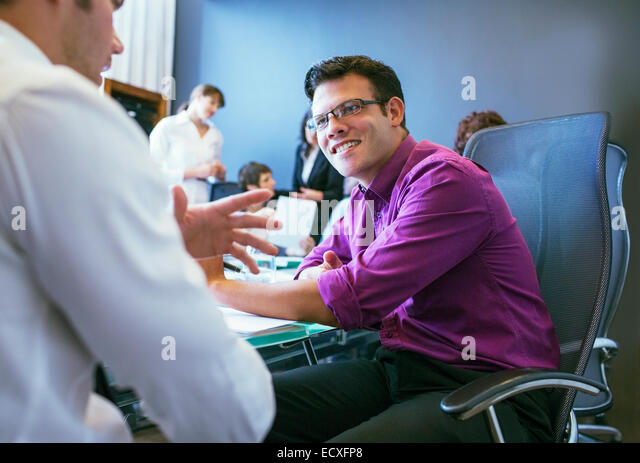 Businessmen talking during meeting in conference room with colleagues in background - Stock-Bilder