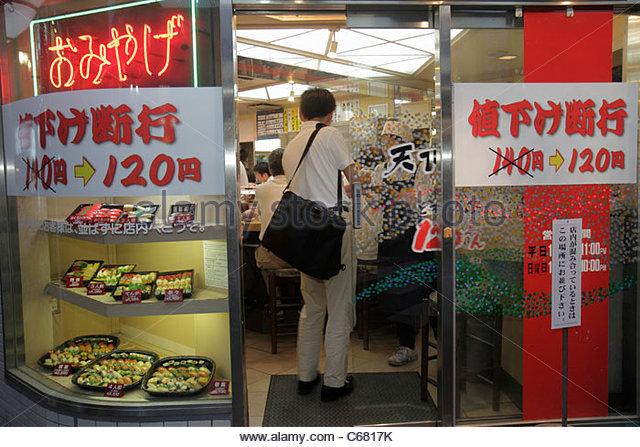 Japan Tokyo Ikebukuro kanji hiragana katakana characters sushi bar restaurant entrance front neon sign - Stock Image
