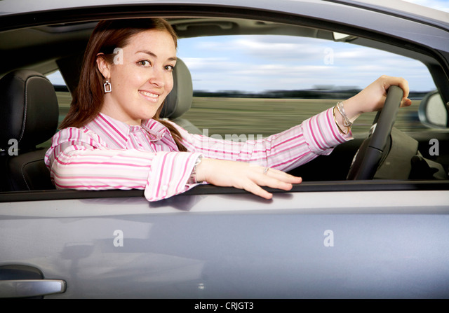 young woman driving a brand new car in left-hand traffic with a smile, United Kingdom, England - Stock Image