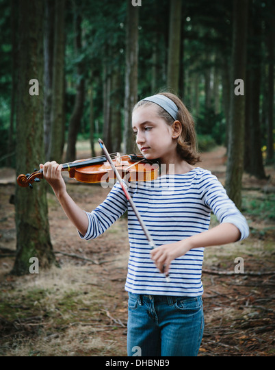 A ten year old girl playing the violin in Discovery Park, Seattle. - Stock Image
